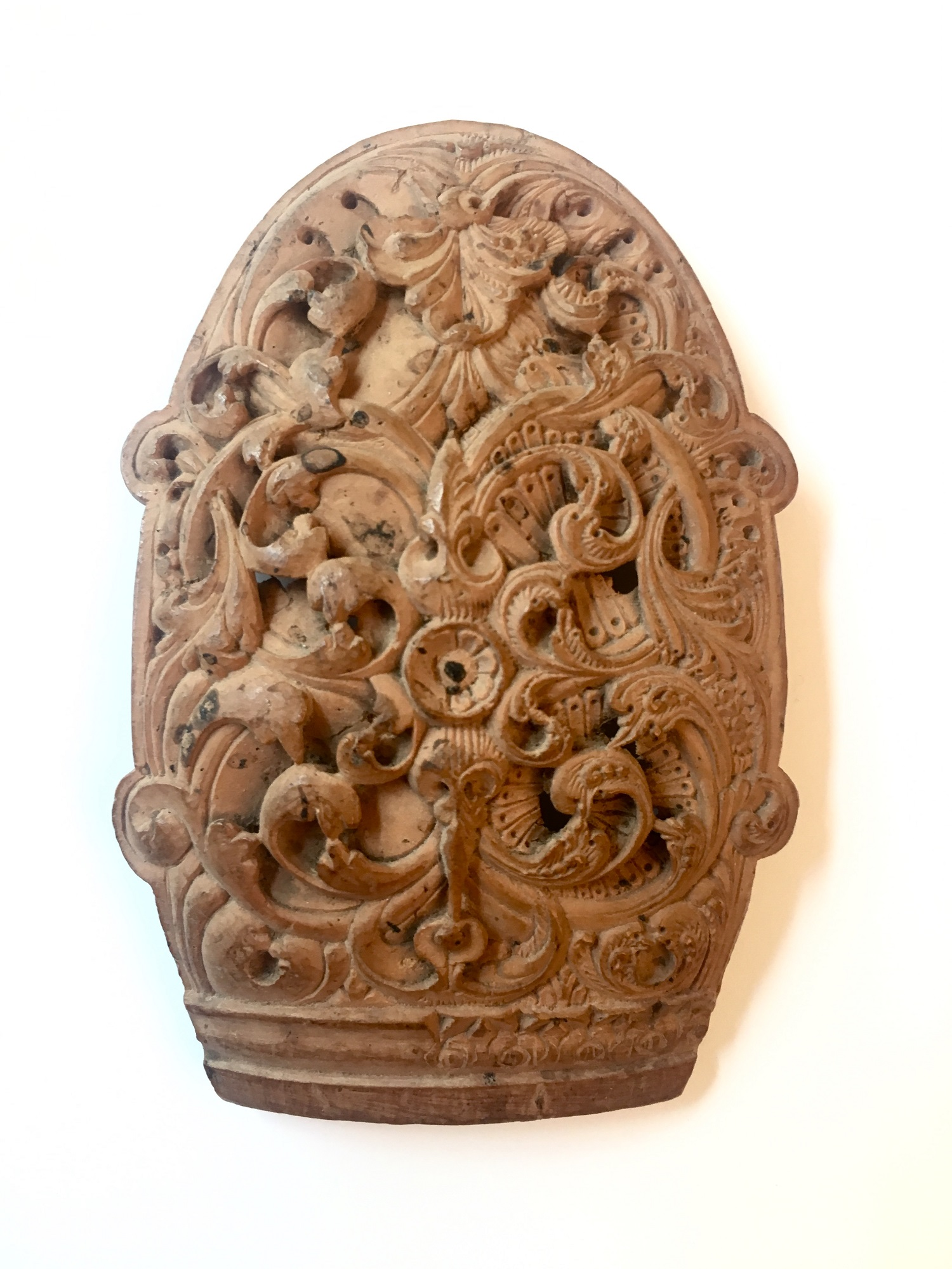 A coconut curved plaque, carved with interweaving scrolling foliage
