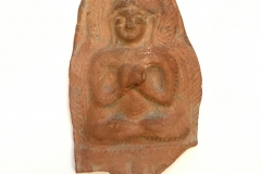 Kashmirian terracotta fragment with seated Buddha with hands in dharmachakra mudra.