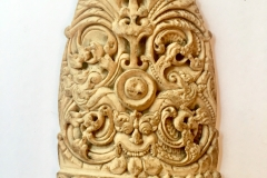 A bone curved plaque , carved with a Kurtimurka and leafy scrolling foliage